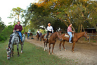 A group of people prepare to set out on a horse back ride in Amelia Island, FL