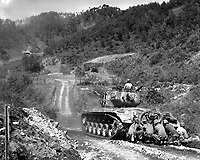 Marine infantrymen take cover behind a tank while it fires on Communist troops ahead.  Hongchon Area, May 22, 1951.  Sgt. John Babyak, Jr. (Marine Corps)<br /> NARA FILE #:  127-N-A8585<br /> WAR & CONFLICT BOOK #:  1420