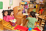 Education preschool boy aiming long block of wood at two girls in pretend play area girls are laughing