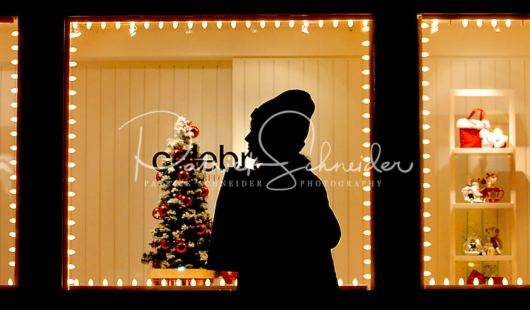 A shopper during the Christmas holiday selling season is silhouetted against a store window at Birkdale Village in Huntersville, NC. Birkdale Village combines the best of shopping, dining, apartments and entertainment venues within a 52-acre mixed-use development.
