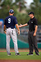 Charlotte Stone Crabs manager Michael Johns (9) talks with umpire Derek Thomas during a game against the Palm Beach Cardinals on July 22, 2017 at Roger Dean Stadium in Palm Beach, Florida.  Charlotte defeated Palm Beach 5-2.  (Mike Janes/Four Seam Images)