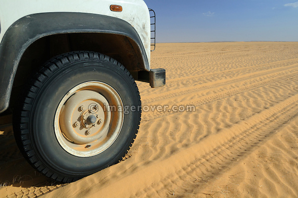 Africa, Mauritania, Sahara Desert, nr. Chinguetti. Land Rover Defender TD5 Station Wagon crossing a sand plain between Chinguetti and Tidjikdja. --- RELEASES AVAILABLE! Automotive trademarks are the property of the trademark holder, authorization may be needed for some uses.