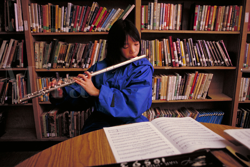 ELEMENTARY SCHOOL BAND PRACTICE - GIRL PLAYING FLUTE. ELEMENTARY SCHOOL STUDENTS. OAKLAND CALIFORNIA USA CARL MUNCK ELEMENTARY SCHOOL.