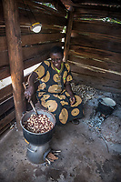 Uganda, Butema. Milly Mugisa (53), uses a Biolite stove at her home, it charges a light and charges her mobile phone. Cooking at home in her kitchen.