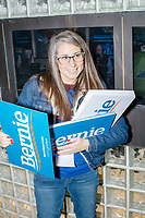 Monica Burke, a volunteer from Acton, Mass., hands out campaign signs before a campaign rally for Democratic presidential candidate and Vermont senator Bernie Sanders at Hampshire Hills Athletic Club in Milford, New Hampshire, on Tue., Feb. 4, 2020. The  event started around 7pm and was the first event Sanders held after the previous day's Iowa Caucuses. The results of the caucuses were unknown until the Democratic party released partial numbers at 5pm, showing Sanders and former South Bend, Ind., mayor Pete Buttigieg both as frontrunners.