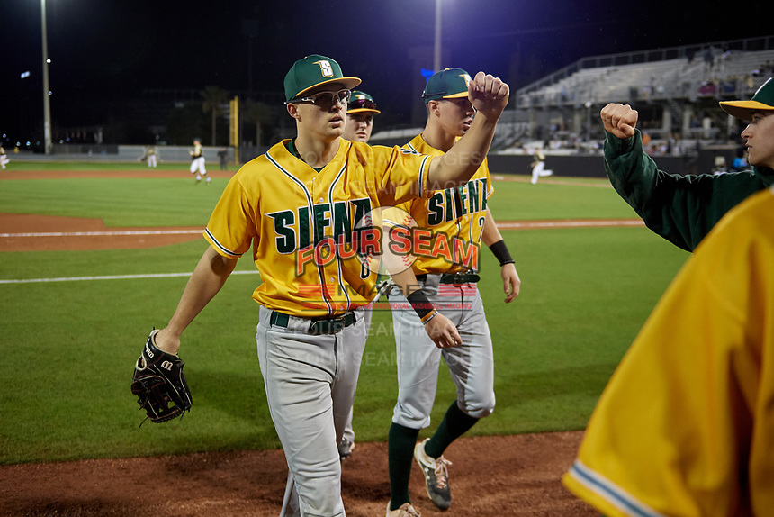Siena Saints Evan St. Claire (8) fist bumps teammates during a game against the UCF Knights on February 14, 2020 at John Euliano Park in Orlando, Florida.  UCF defeated Siena 2-1.  (Mike Janes/Four Seam Images)