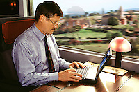 Businessman using laptop computer in First  Class carriage on Eurostar the high speed train which travels through the Channel Tunnel between London and Paris and London and Brussels