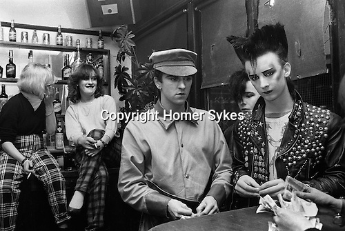 """Steve Strange, Boy George and friend Wilf Rogers.( behind George) End of the evening, counting out money. Blitz Kids New Romantics at The Blitz Club Covent Garden, London, England 1980. George is wearing a Malcolm McLaren cowboys t-shirt from Seditionaries based on a Jim French drawing.<br /> <br /> In reality George O'Dowd,had not assumed the name """"Boy George"""", at this time. He told me he was known as just George."""