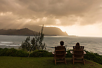 A couple watches the sun set over Mount Makana (nicknamed Bali Hai) and rest of the mountain range, Princeville, Kaua'i.