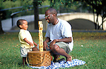 smiling father and toddler son playing and picnicking in park