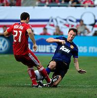 Manchester United defender Jonny Evans (23) goes in for the slide tackle against Chicago Fire midfielder Michael Videira (21).  Manchester United defeated the Chicago Fire 3-1 at Soldier Field in Chicago, IL on July 23, 2011.