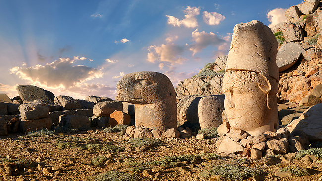 Statue heads at sunrise, from right,  Antiochus & Eagle  in front of the stone pyramid 62 BC Royal Tomb of King Antiochus I Theos of Commagene, east Terrace, Mount Nemrut or Nemrud Dagi summit, near Adıyaman, Turkey