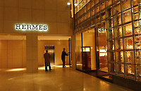 People shop and pass luxury French store Hermes in Ginza district of Tokyo..