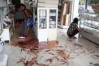 Staff at an electronics shop in the border town of Mae Sai clean the blood-soaked floor. The blood is from a 42 year old women who was injured by shrapnel the previous day. An estimated 20,000 Burmese refugees fled into Thailand to escape clashes in the border towns of Myawaddy and Pyaduangsu, only a day after a Burmese election which critics described as a sham..Ethnic minorities along the Thai-Burma border had warned earlier that the junta would launch a major offensive after the election, as many armed rebel groups had refused to become part of the government-controlled Border Guard Forces.