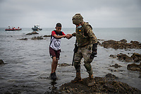 CEUTA, SPAIN ‐ MAY 19: A Spanish soldier helps a migrant as he leaves the water on the Tarajal beach, after having crossed the border between Morocco and Spain swimming on May 19, 2021 in Ceuta, Spain.  After a diplomatic conflict between Spain and Morocco, thousands of migrants who have taken advantage of the little Moroccan police activity on the border to cross it mainly by swimming, which has caused a migration crisis with the entry of more than 8000 migrants from the African country. (Photo by Joan Amengual/VIEWpress )