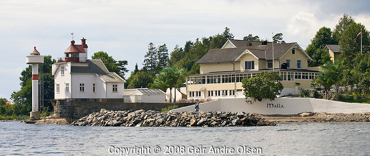 The lighthouse at Filtvet at the entrance to Oslo fjord at Hurum, just outside Oslo, Norway. The restaurant Villa Malla to the right