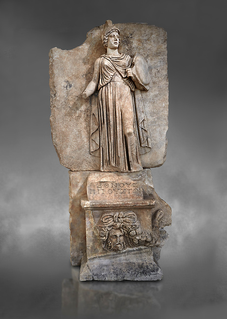 "Roman Sebasteion relief sculpture personifing a Balkan Warrior  Aphrodisias Museum, Aphrodisias, Turkey.  Against a grey background.<br /> <br /> The relief figure personifies a Balkan Warrior tribe defeated by Tiberius in AD 6-8 before he became emperor. She wears a classical dress, cloak and helmet and carries a small shield and probably once a spear. A builder's inscription, ""Pirouston"", written above the shield, ensured the relief was put on the right base"