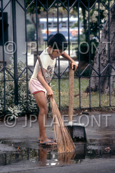 Child is employed to clean the street in Manilla, Philippines - Child labor as seen around the world between 1979 and 1980 - Photographer Jean Pierre Laffont, touched by the suffering of child workers, chronicled their plight in 12 countries over the course of one year.  Laffont was awarded The World Press Award and Madeline Ross Award among many others for his work.