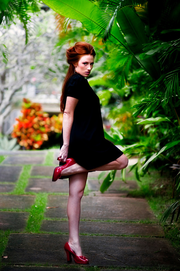 Fashion Photography by Liisa Roberts. Red Headed flamingo stance. Little black dress. Thrift Store Fashion finds.  Vintage wear. Reduce, Reuse, Recycle, ReFashion.  Red heels.
