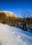 A hiker standing on a bridge along the Franconia Notch Bike Path in Franconia Notch, New Hampshire during the winter months. Cannon Mountain is in the background.