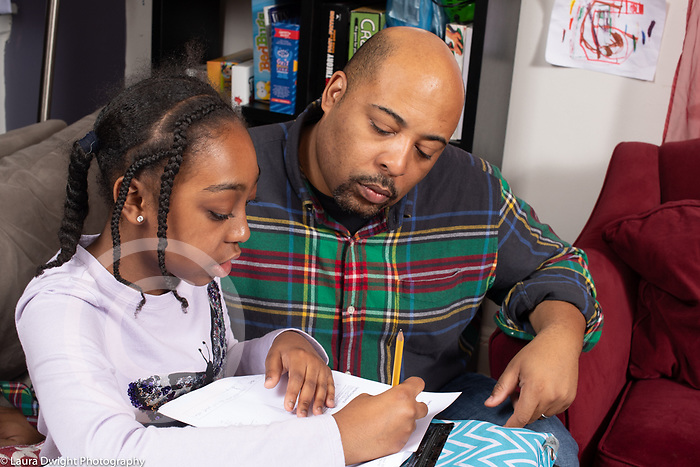 11 year old girl at home with father, doing homework
