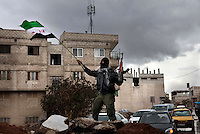 A disguised member of the Free Syrian Army, an armed group that has risen up against the regime of President Bashar al-Assad, waves an AK47 and a pre-Ba'ath regime Syrian flag in the Sakba district of Damascus. The Free Syrian Army claims to be predominately made up of deserters from the regular army who objected to being called on to shoot protesting civilians.