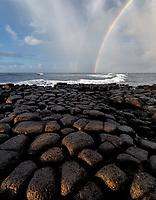 Basalt columns and rainbow with storm clouds. Kauai, Hawaii