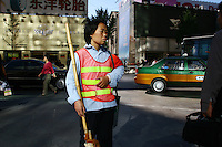 CHINA. Beijing. A street cleaner on the Wangfujing shopping street in central Beijing. 2006.