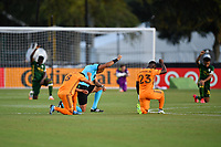 LAKE BUENA VISTA, FL - JULY 18: Houston Dynamo and Portland Timbers players and referee Ismail Elfath take a knee during a game between Houston Dynamo and Portland Timbers at ESPN Wide World of Sports on July 18, 2020 in Lake Buena Vista, Florida.