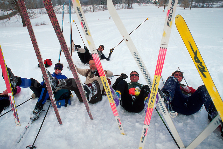 A group of friends clowning around on their cross-country skis, pretending they've all fallen down.
