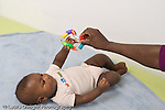 5 month old baby boy African American on back horizontal reaching for toy his mother is holding out