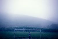 Student goes to rural school early in the morning and crosses a soccer field next to sugarcane plantation under fog in the rural area of Palmares city in Pernambuco State, Brazil.