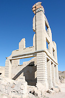 The remains of the Cook Bank Building still dominate the Rhyolite skyline just as it did when it was built in the early 1900's at a cost of $90,000. The building had marble floors imported from Italy, mahogany woodwork, electrict lights, telephone, and inside plumbing. By 1910 parts off the building were being sold off and by 1919 the building was no longer in use. Photographed 03/08