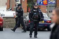 """Pictured: Police officers in the car park next to the Lloyds Bank on the High Street of Gorseinon, Wales, UK. Tuesday 20 November 2018<br /> Re: Two men with machetes are being hunted by police after trying to rob a Lloyds Bank in Gorseinon, near Swansea.<br /> Armed officers, police dogs and helicopter responded to the armed robbery at 10:00am on Tuesday.<br /> According to witnesses reports, the robbers """"came through the ceiling"""" and held a member of staff by the throat.<br /> South Wales Police said nobody was hurt during the incident.<br /> A witness said: """"They had a girl from Lloyds by the throat. After robbing the bank they used a car to drive off."""""""