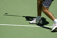 Shadow of a tennis player hitting the ball on the court.