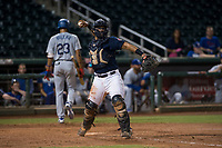 AZL Indians 2 catcher Felix Fernandez (9) prepares to make a throw to first base after a strike out as Leonel Valera (23) walks back to the dugout during an Arizona League game against the AZL Dodgers at Goodyear Ballpark on July 12, 2018 in Goodyear, Arizona. The AZL Indians 2 defeated the AZL Dodgers 2-1. (Zachary Lucy/Four Seam Images)