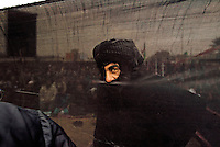 An Iraqi Shiite man talks to another through a hole in a cloth screen outside a mosque in Sadr City, a predominantly Shiite neighborhood of Baghdad, during Friday prayers Feb. 11, 2005. Holes are cut into the cloth screen in order for the wind to pass freely.