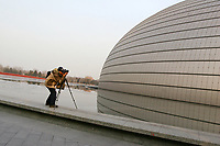 CHINA. Beijing.A photographer photographing an outside view of the Grand National Theatre. Designed by French architect Paul Andreu, The Grand National Theatre is located near Beijing's central Tian'anmen Square. It is an enormous glass and titanium tear-drop-like bubble structure surrounded by water. As China's top art performance center, it covers a total floor space of around 180,000 square meters, including 130,000 square meters for the main building and 50,000 square meters underground facilities. 2008.