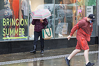 """Pictured: A shopper with an umbrella, walks past a """"Bring On Summer"""" shop window outside the Marks and Spencer store, Oxford Street, Swansea, Wales, UK. <br /> Re: A yellow warning has been forecast by the Met Office, from 6am until midnight on Saturday, for rain affecting south, west and parts of mid Wales, UK."""