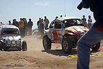 RACE CARS AND ON LOOKERS AT BAJA AUTO RACE