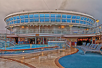 A rainy view of the pool on the deck of the Emerald Princess.