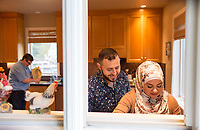 """SEATTLE, WA-APRIL 17, 2017: Hussein Saab says he likes to look over his wife's shoulder when she cooks. They are co-hosting a """"dinner with your Muslim neighbor"""" at the home of Stefanie and Nason (cq) Fox (left, background) in Seattle, WA on a return trip April 17th 2017. The couple now live in Detroit. <br /> (Photo by Meryl Schenker/For The Washington Post)"""