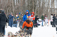 Travis Beals and team run past spectators on the bike/ski trail near University Lake with an Iditarider in the basket and a handler during the Anchorage, Alaska ceremonial start on Saturday, March 7 during the 2020 Iditarod race. Photo © 2020 by Ed Bennett/Bennett Images LLC