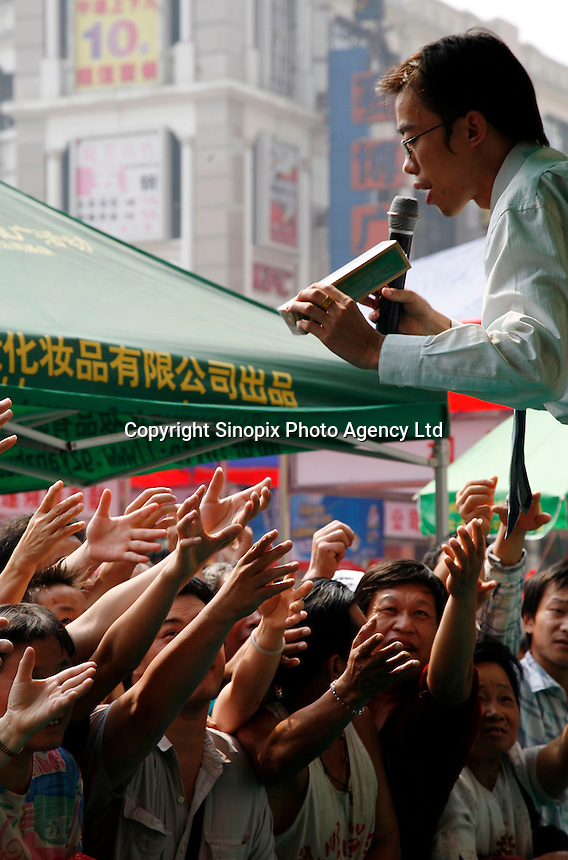 """An audience eagerly grabs for boxes of supposedly """"giveaway"""" shampoo, which later turns out to be sales items, at a square in Guangzhou, Guangdong Province, China. .10 Nov 2006"""