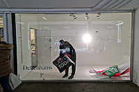 """A store employee removes a """"Last Day Today"""" poster from the window of the Debenhams store which has now closed for the last time in Swansea, Wales, UK. Saturday 15 May 2021"""