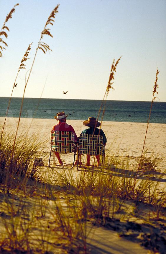Senior couple sitting on beach on Gulf of Mexico. Gulf Shores Alabama United States.
