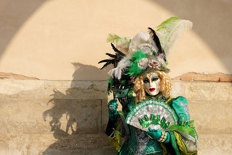 Woman dressed in traditional mask and costume for Venice Carnival standing under arch at Doge's Palace, Piazza San Marco, Venice, Veneto, Italy