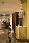 Harrods Department store. Statue of Mr Al Fayed chairman of Harrods, boy has photoghraph taken.