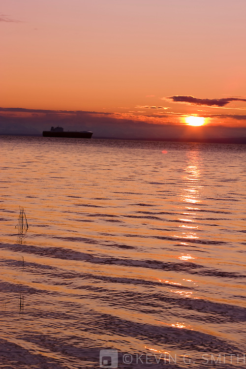Cargo Ship sailing up Knik Arm towards the Port of Anchorage to unload, high tide, sunset, Anchorage, Scouthcentral Alaska, USA.