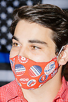 A man wears a facemask decorated with GOP and Republican party buttons in front of a Blue Lives Matter flag on the wall as people gather for a Trump campaign office opening party in Salem, New Hampshire, on Fri., Sept. 18, 2020. Former 2016 Trump campaign manager and current 2020 Trump campaign senior advisor Corey Lewandowski, lives in nearby Windham, NH, spoke at the event, which also doubled as a surprise birthday celebration for Lewandowski.